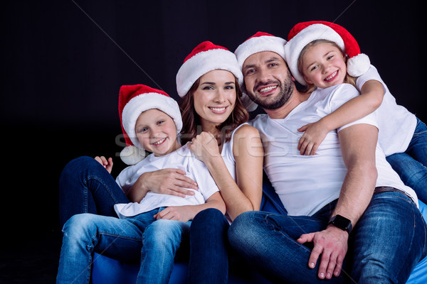 family in Santa hats looking at camera Stock photo © LightFieldStudios