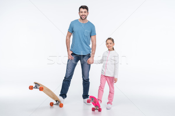 smiling father and daughter standing with skateboards on white Stock photo © LightFieldStudios