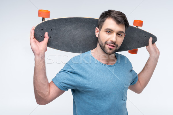 portrait of man holding skateboard in hands on white Stock photo © LightFieldStudios