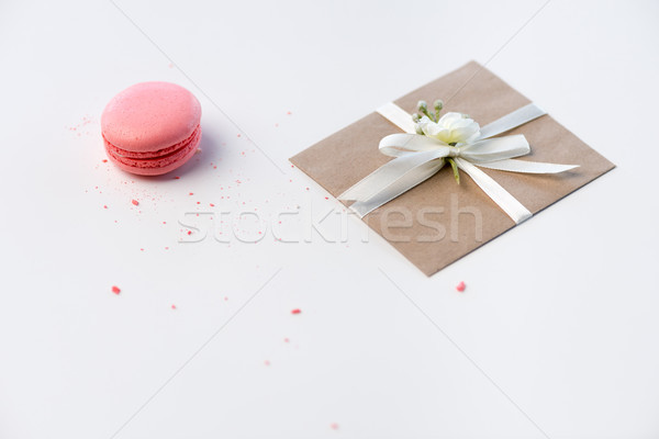 Close-up view of decorative kraft envelope with bow and pink macaron isolated on white, wedding invi Stock photo © LightFieldStudios