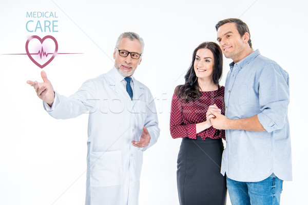 doctor pointing at medical care icon Stock photo © LightFieldStudios