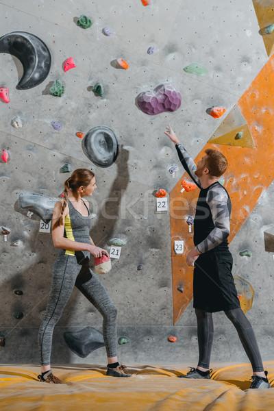 young man pointing to climbing wall Stock photo © LightFieldStudios