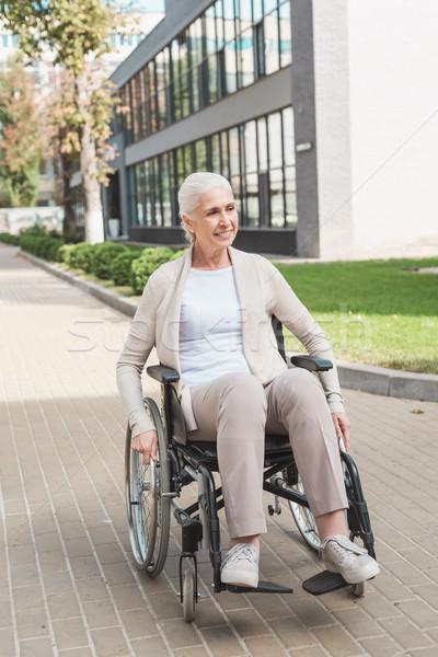 Idős nő tolószék mosolyog ül másfelé néz Stock fotó © LightFieldStudios