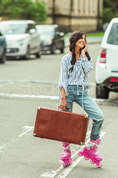Stock photo: girl in roller skates with smartphone and suitcase