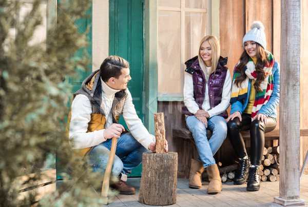 Smiling young women looking at handsome man chopping firewood with axe on porch   Stock photo © LightFieldStudios