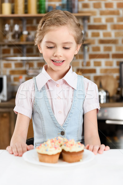 Cute smiling little girl looking at tasty cakes on plate Stock photo © LightFieldStudios