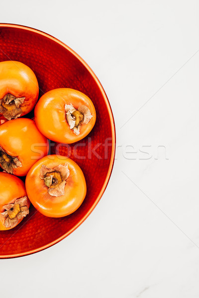 top view of persimmons on red plate isolated on white Stock photo © LightFieldStudios