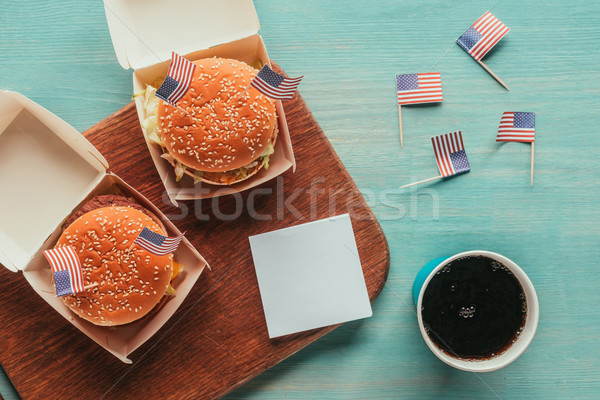 top view of arranged burgers and soda drink with american flags on wooden tabletop, presidents day c Stock photo © LightFieldStudios