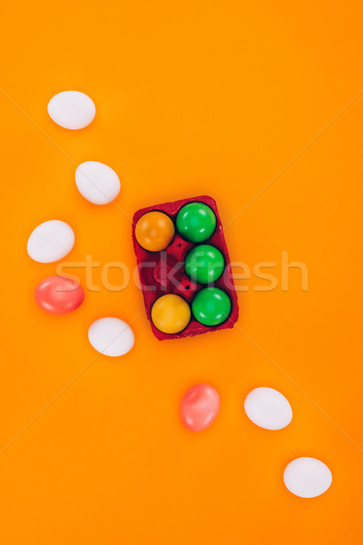 top view of colored easter eggs in red egg tray isolated on orange Stock photo © LightFieldStudios