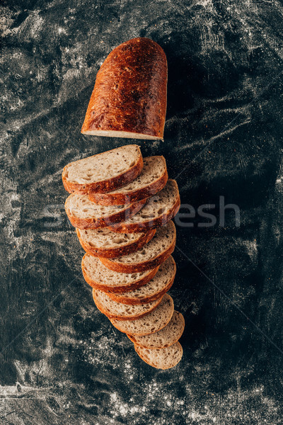 top view of arranged pieces of bread on dark surface with flour Stock photo © LightFieldStudios