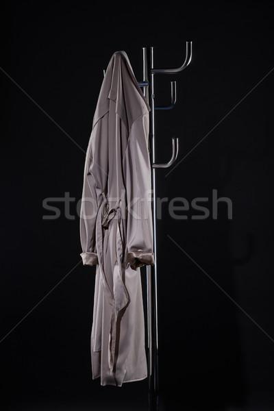 Tranchée manteau suspendu rack isolé noir Photo stock © LightFieldStudios