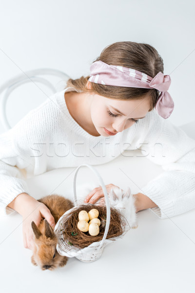 high angle view of girl looking at rabbits and basket with easter eggs in nest Stock photo © LightFieldStudios