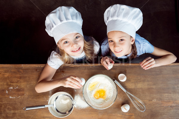Stock photo: overhead view of girls making dough for cookies on wooden table
