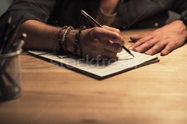 Muzikant schrijven muziek notebook shot man Stockfoto © LightFieldStudios