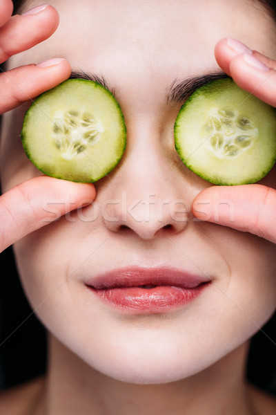 woman applying cucumber eye mask Stock photo © LightFieldStudios