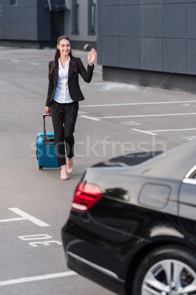 Woman walking with suitcase in parking lot Stock photo © LightFieldStudios