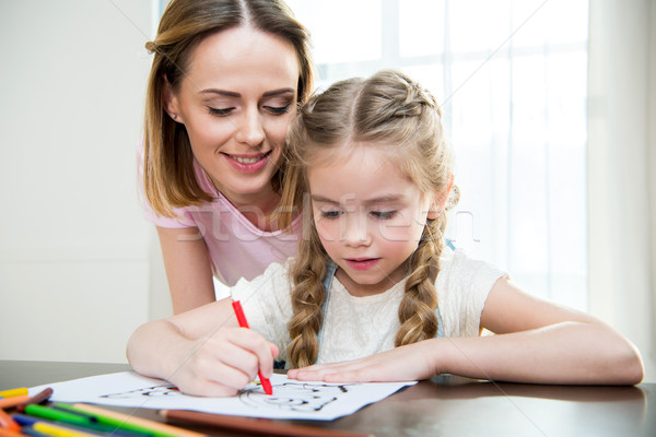 Happy mother and cute little daughter drawing at table Stock photo © LightFieldStudios