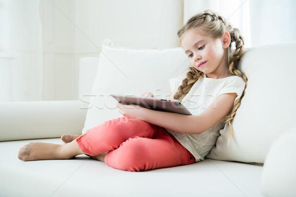 Oldalnézet fókuszált lány ül kanapé tabletta Stock fotó © LightFieldStudios