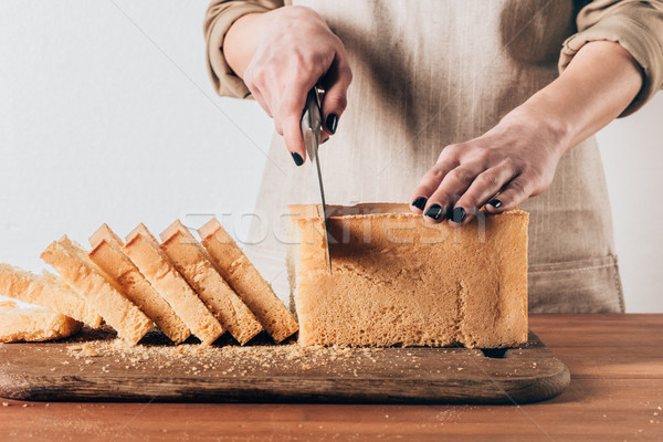 partial view of woman cutting loaf of bread on wooden cutting board Stock photo © LightFieldStudios