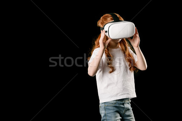 girl using virtual reality headset isolated on black Stock photo © LightFieldStudios