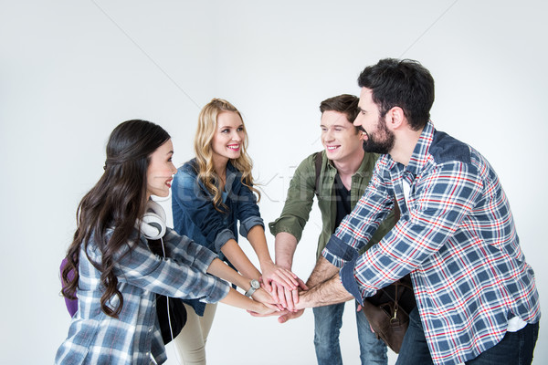 four young students in casual clothes stacking hands on white Stock photo © LightFieldStudios