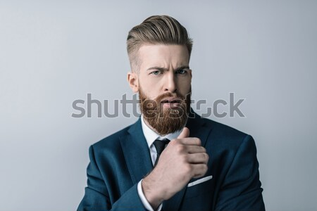 Stylish bearded businessman frowning and looking at camera Stock photo © LightFieldStudios
