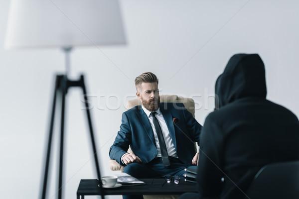 Fiatal szakállas üzletember beszél anonim személy Stock fotó © LightFieldStudios