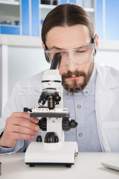Homem olhando microscópio moço óculos laboratório Foto stock © LightFieldStudios