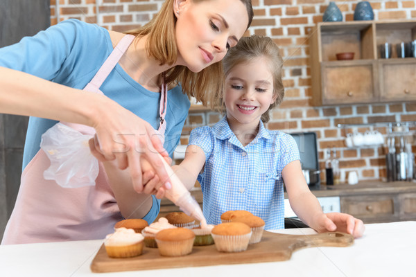 portrait of mother putting cream on cupcakes with daughter near by Stock photo © LightFieldStudios