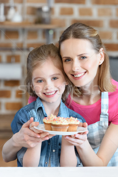 portrait of smiling mother and daughter holding plate with cupcakes Stock photo © LightFieldStudios