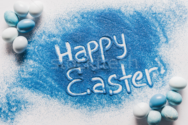 top view of happy easter sign made of blue sand with painted eggs on white Stock photo © LightFieldStudios