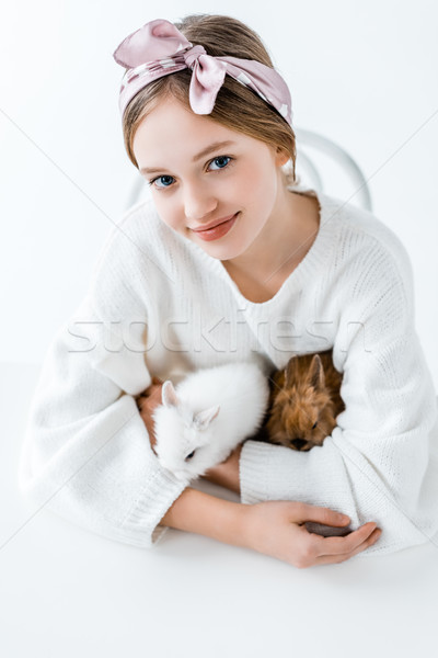 cute happy girl holding furry rabbits and smiling at camera on white Stock photo © LightFieldStudios