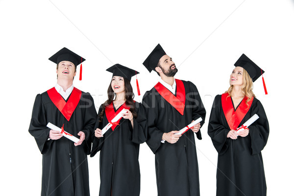 Group of young men and women in graduation gowns and mortarboards holding diplomas Stock photo © LightFieldStudios