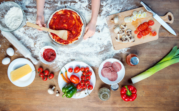 top view of child making pizza with pizza ingredients, tomatoes, salami and mushrooms on wooden tabl Stock photo © LightFieldStudios