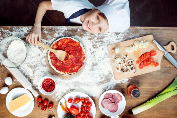 top view of boy making pizza with pizza ingredients, tomatoes, salami and mushrooms on wooden tablet Stock photo © LightFieldStudios