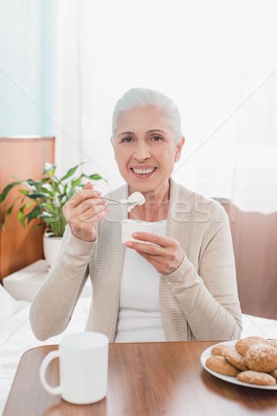 Senior donna mangiare yogurt sorridere Foto d'archivio © LightFieldStudios