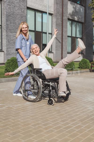 Foto stock: Enfermeira · senior · mulher · cadeira · de · rodas · sorridente