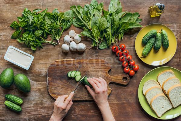 woman cutting cucumber for breakfast Stock photo © LightFieldStudios