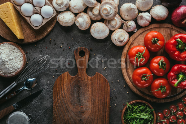 top view of different raw ingredients for pizza and cutting board on concrete surface Stock photo © LightFieldStudios