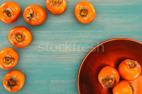 top view of persimmons on red plate and turquoise table Stock photo © LightFieldStudios