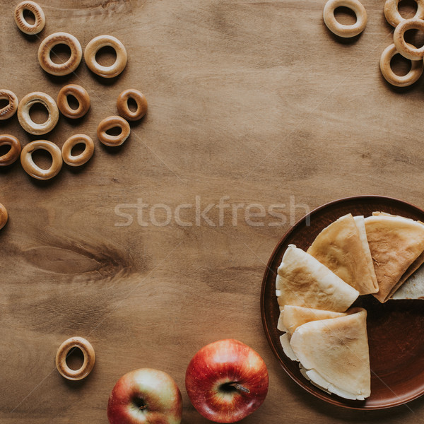 top view of tasty homemade pancakes with apples and bagels on wooden table Stock photo © LightFieldStudios