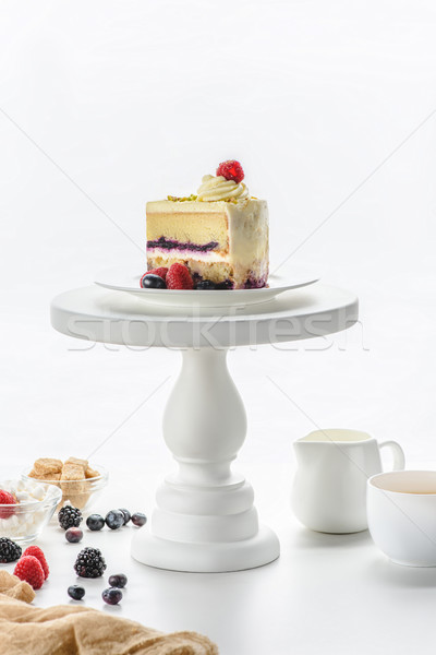 piece of cake on white cake stand, coffee on table Stock photo © LightFieldStudios