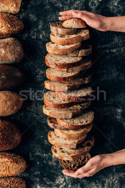 cropped shot of female hands and arranged pieces of bread on dark tabletop Stock photo © LightFieldStudios