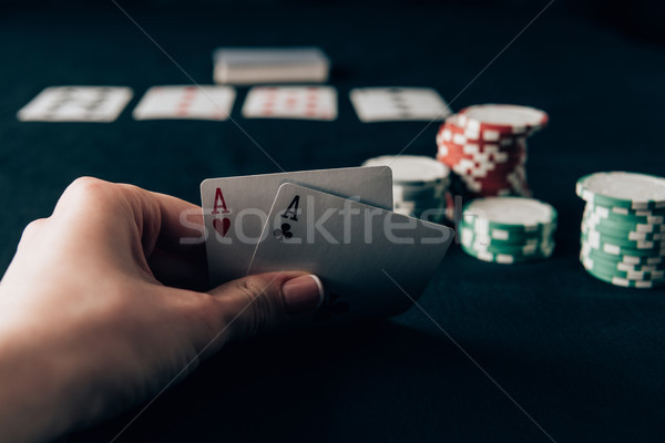 Woman holding playing cards by casino table Stock photo © LightFieldStudios