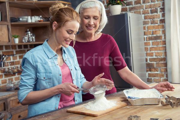 Grandmother and granddaughter sifting flour Stock photo © LightFieldStudios