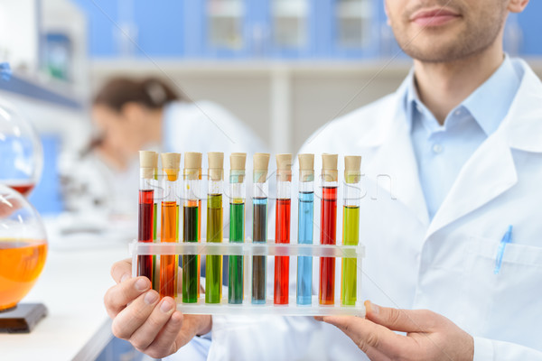 Close-up partial view of scientist holding test tubes with reagents in lab Stock photo © LightFieldStudios