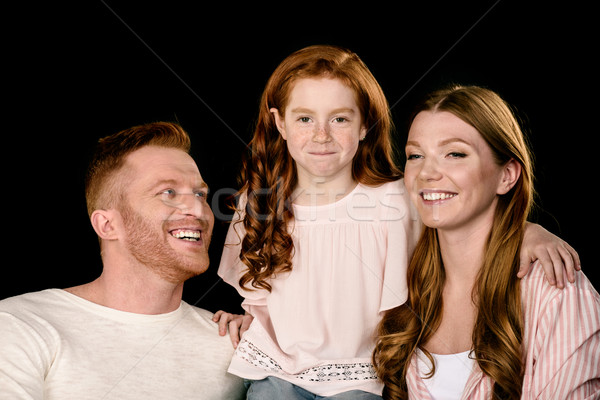 Happy parents with adorable little daughter smiling and embracing isolated on black Stock photo © LightFieldStudios