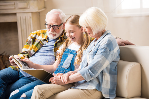 Happy grandparents and smiling granddaughter sitting on sofa and looking at photo album Stock photo © LightFieldStudios