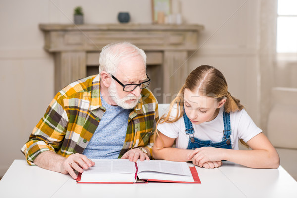 Grandfather and granddaughter sitting at table and reading book together Stock photo © LightFieldStudios