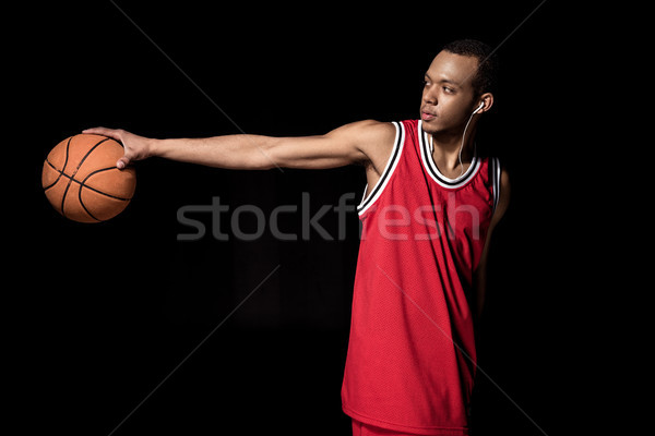 Young athletic basketball player in earphones holding ball on black Stock photo © LightFieldStudios
